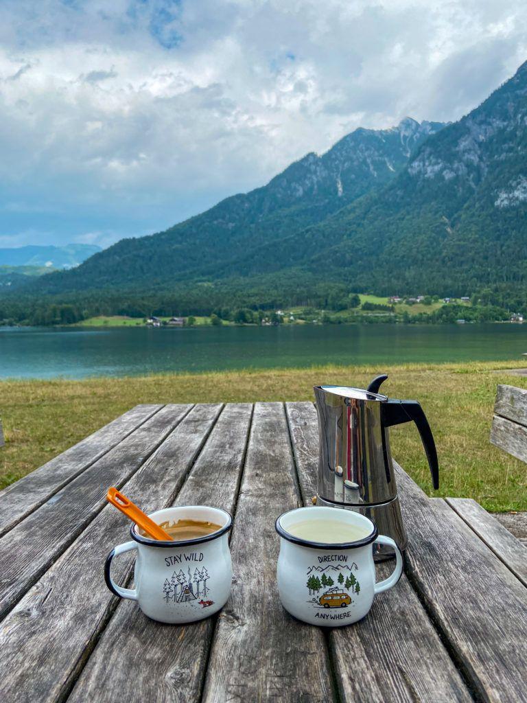 Dwa metalowe kubki i kawiarka stoją na stole, a w tle jest Jezioro Halsztackie