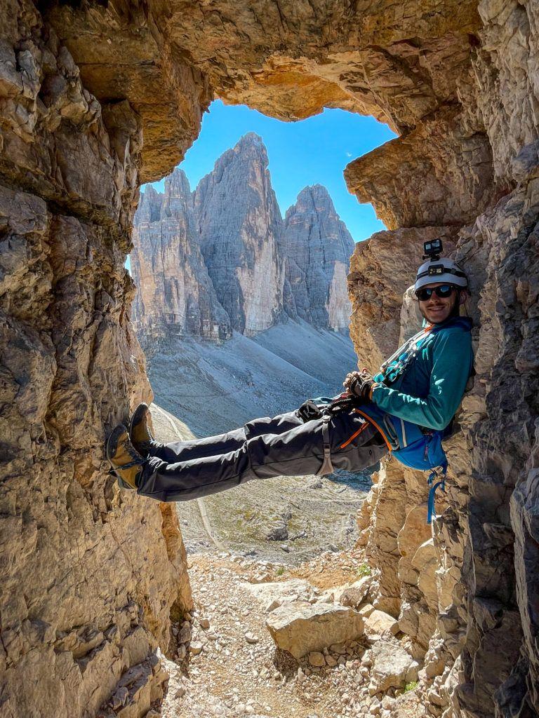 Marcin zaparty nogami o skały z widokiem na Tre Cime