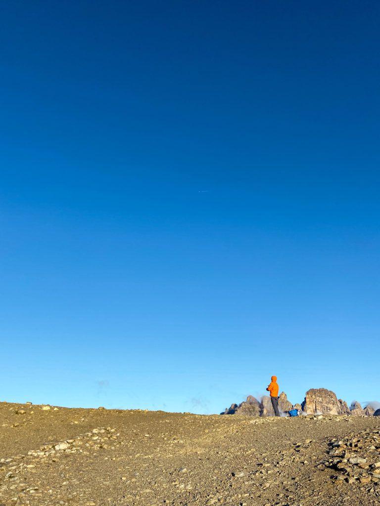 Marcin stoi na Przełęczy Lavaredo, za nim jest niebieskie niebo