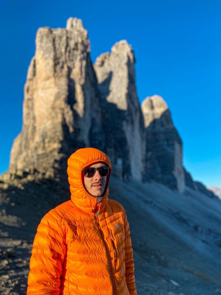 Marcin stoi w pomarańczowej kurtce, a za nim jest Tre Cime di Lavaredo