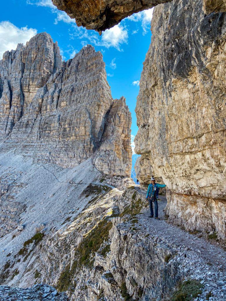 Marcin stoi na półce skalnej podczas zejścia z Monte Paterno